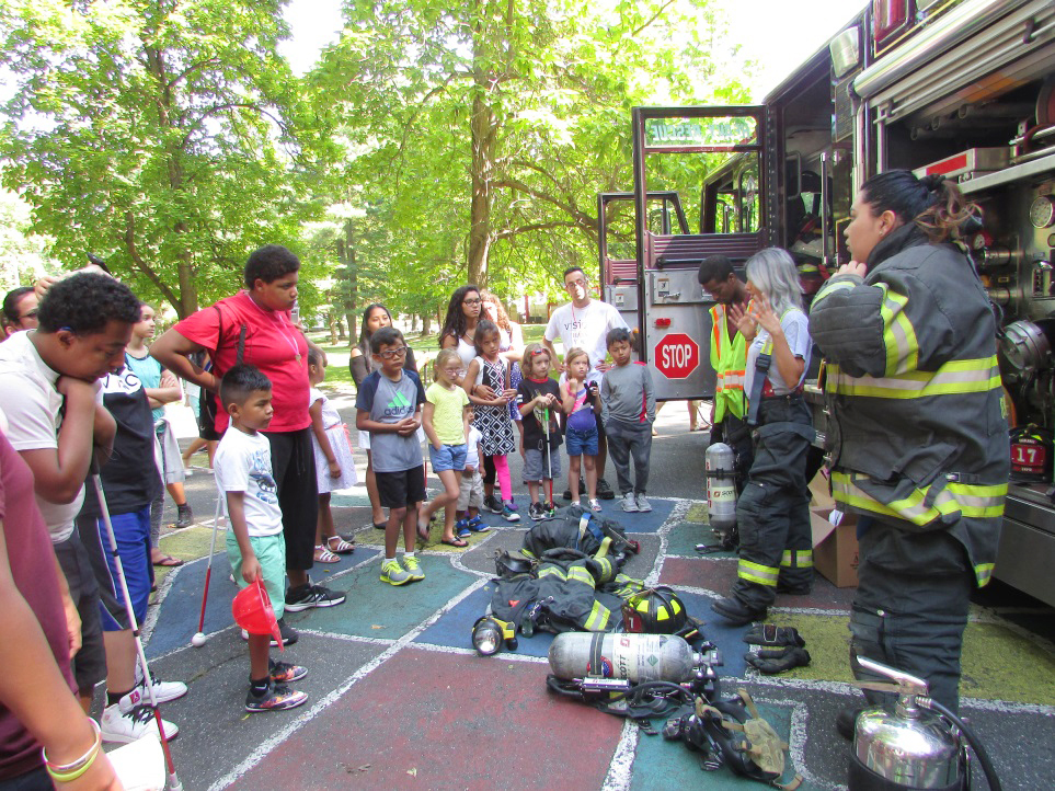 firewomen and fireman showing off their equipment next to the fire engine in front of a crowd of children and adults