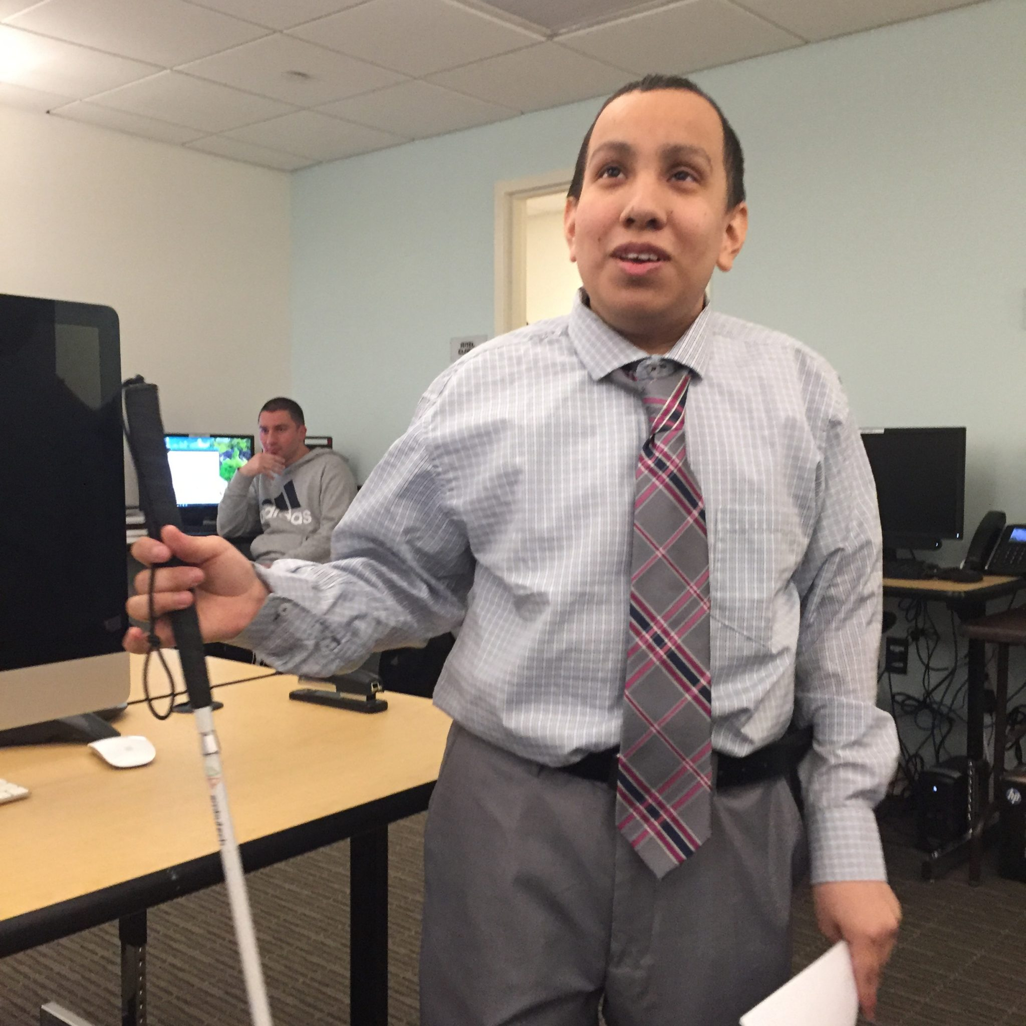 Image description: A young man holding a cane with one hand, and a piece of paper in the other, wearing a light gray button downshirt, gray and red plaid tie, and gray pants stands inside a computer lab.