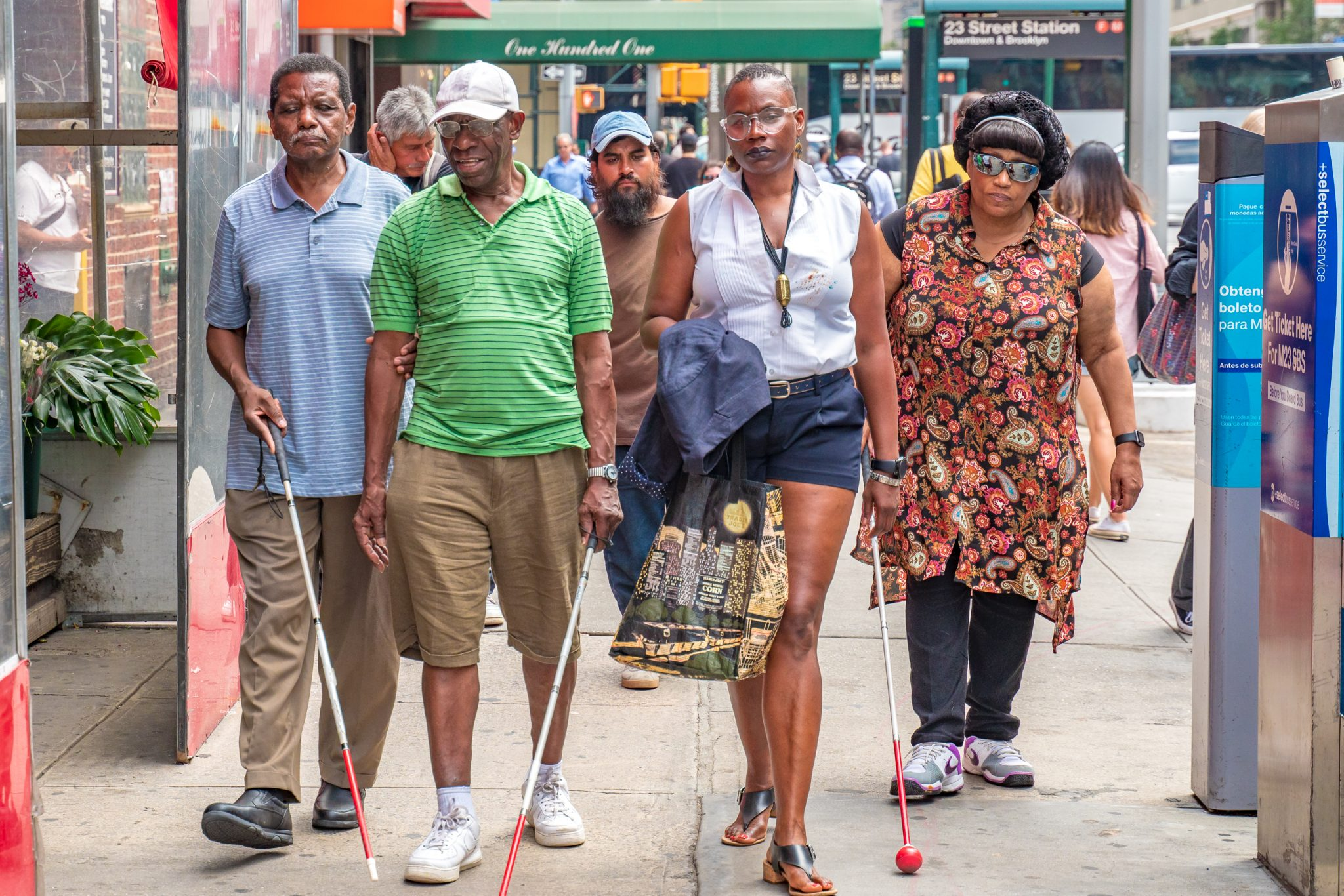 Image description: A group of four people, 2 older men (left), an orientation and mobility instructor (right), and an older woman (far right) walk down a city block.