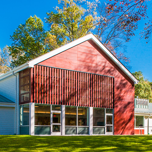 Image description: An exterior view of VISIONS Vocational Rehabilitation Center. A large red barn-shaped building surrounded by trees, on a large grassy field.