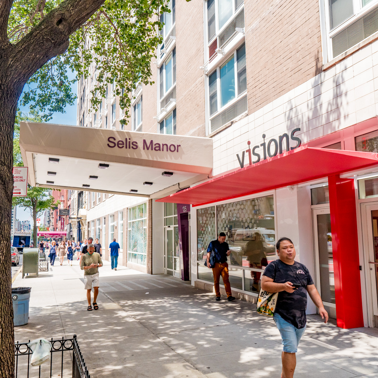 Image description: An exterior view of the entrance to VISIONS at Selis Manor. The front of a beige building has a large red awning with the VISIONS logo above it.