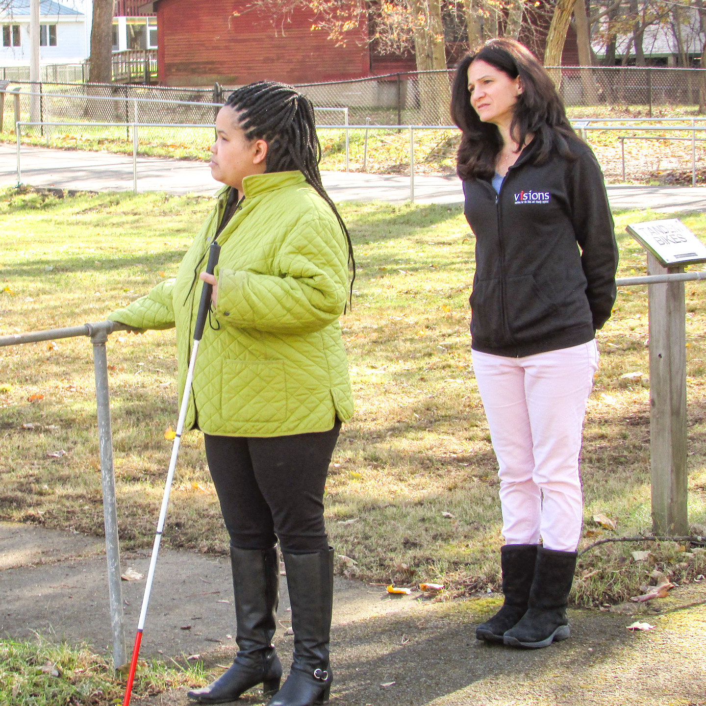 Image description: A woman holding her cane in one hand (left) holds onto a fence with the other, as her female instructor (right) stands behind her