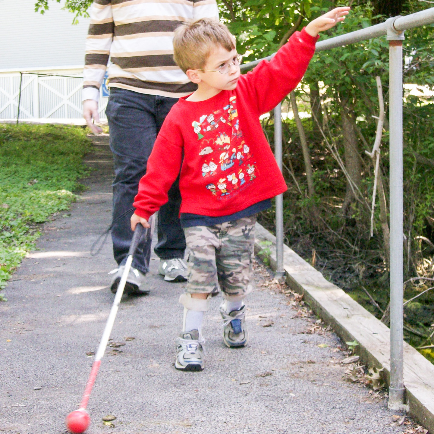 Image description: A young boy holding a cane walks down a street parallel to a fence.