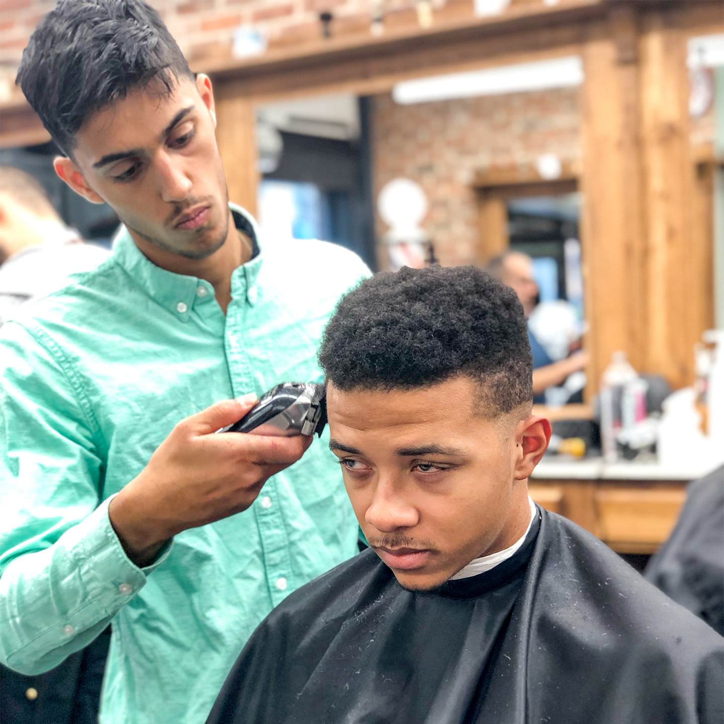 A barber (left) uses a trimmer to style the hair of a young man (right) sitting in a chair.