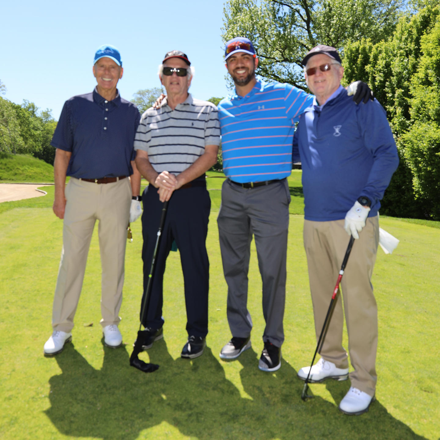 Four golfers, two of whom are holding their clubs stand together surrounded by trees and a bright blue sky.