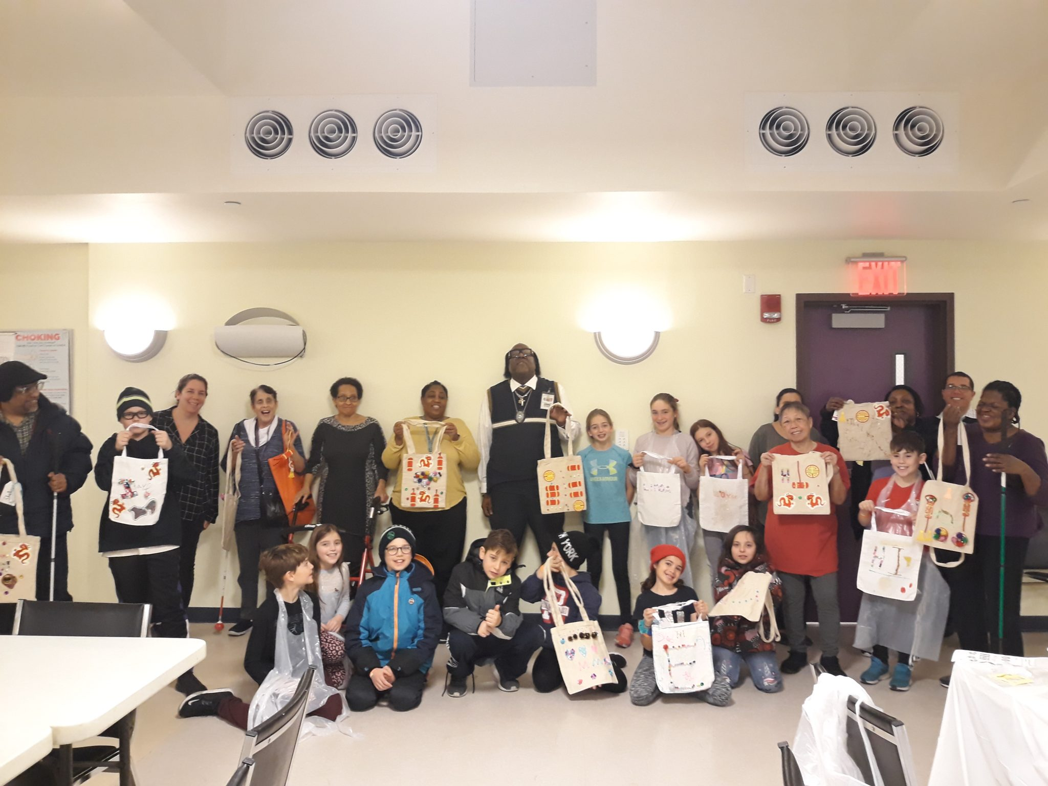 A large group of young children and VISIONS Center on Aging participants stand and pose for a group photo