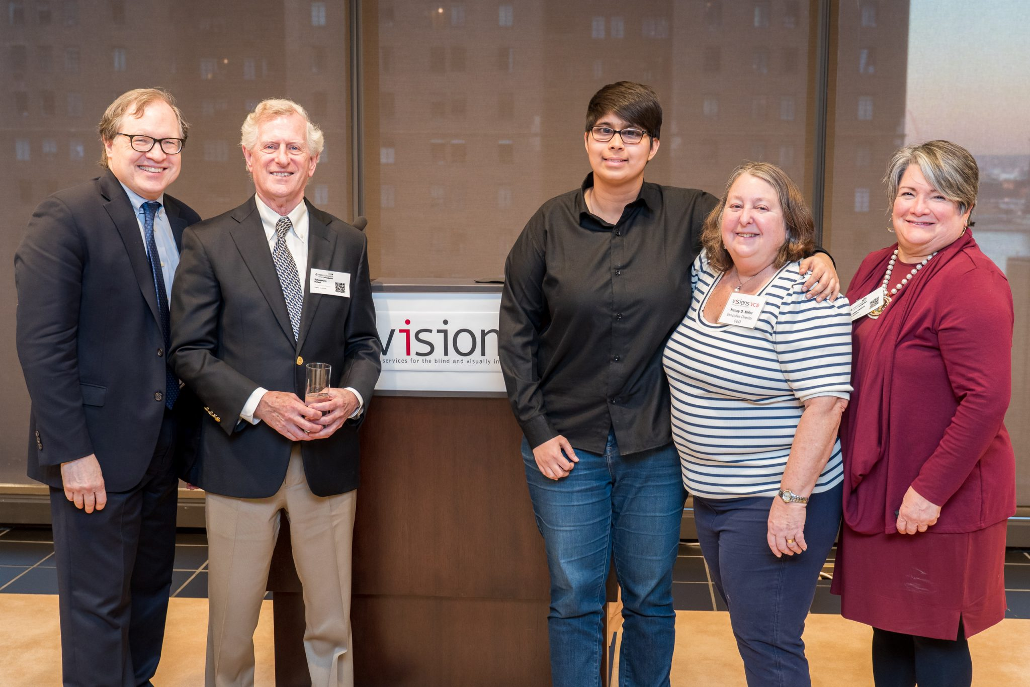 A group of five people stand together in front of a podium bearing the VISIONS logo