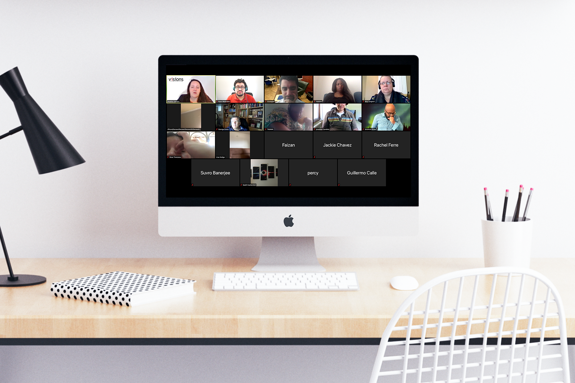 An iMac sits on a desk, its screen showing a Zoom video call in progress with 19 participants.