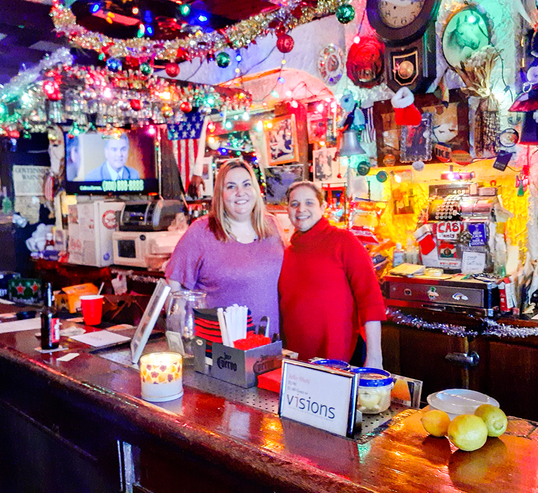 Two women stand behind a bar decorated with bright lights, photos, knick knacks, and sparkly ribbons