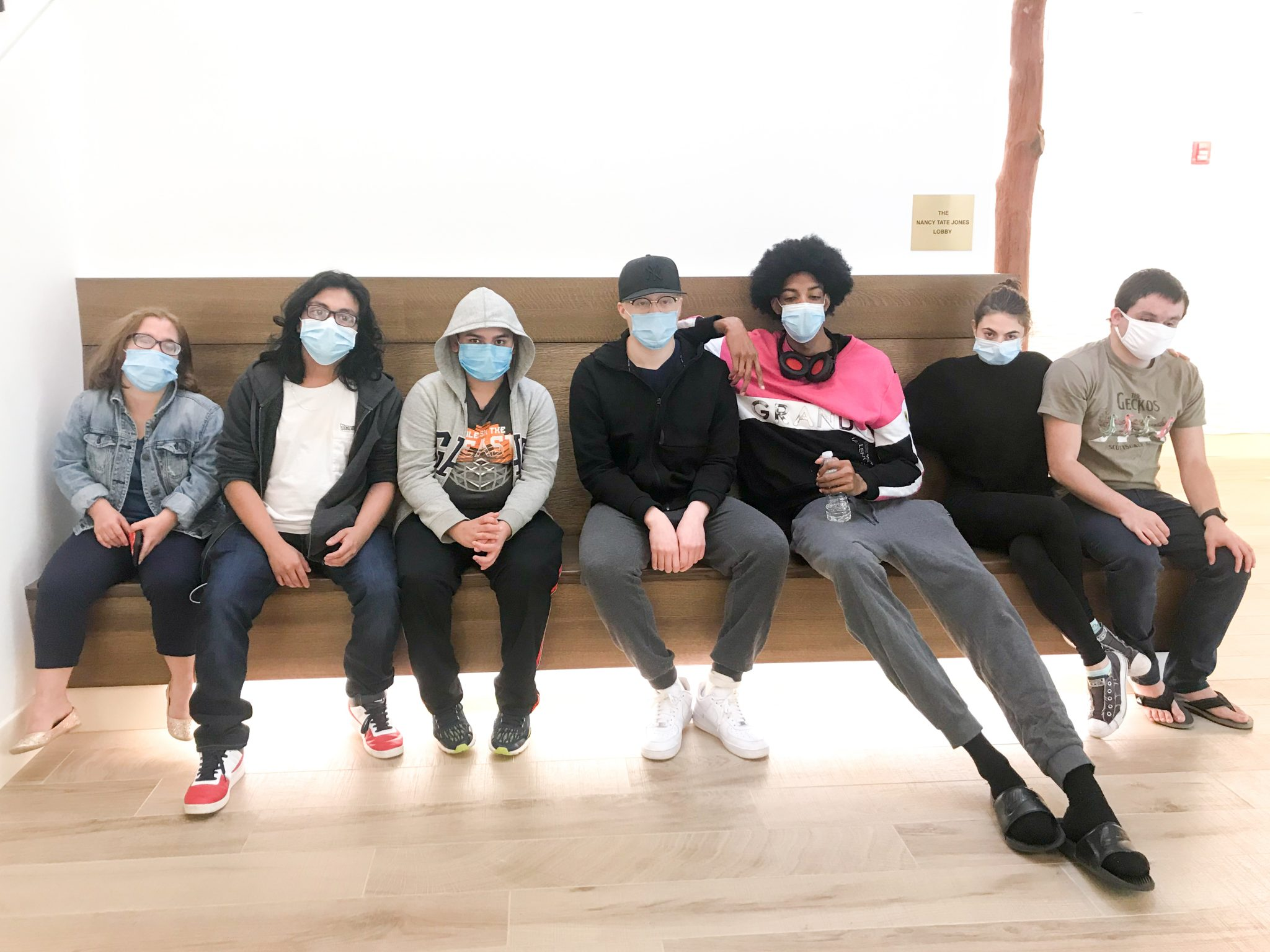 A group of seven participants wearing masks sit inside of VISIONS Vocational Rehabilitation Center's lobby.