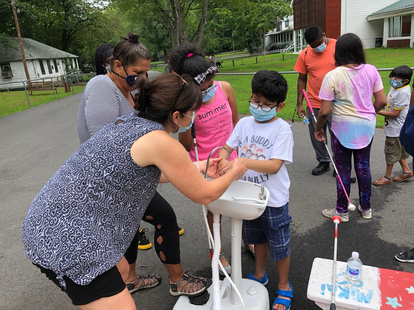 Children and adults line up by an outdoor sink as one of VCB's staff helps one of the children properly wash their hands.
