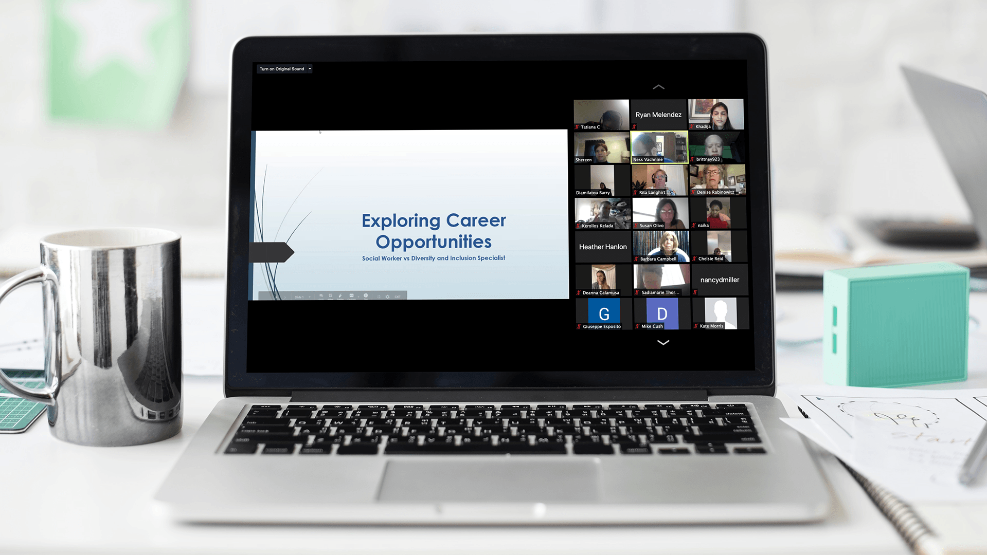 A laptop features a Zoom conference with a PowerPoint on screen, being shared with more than 21 participants.