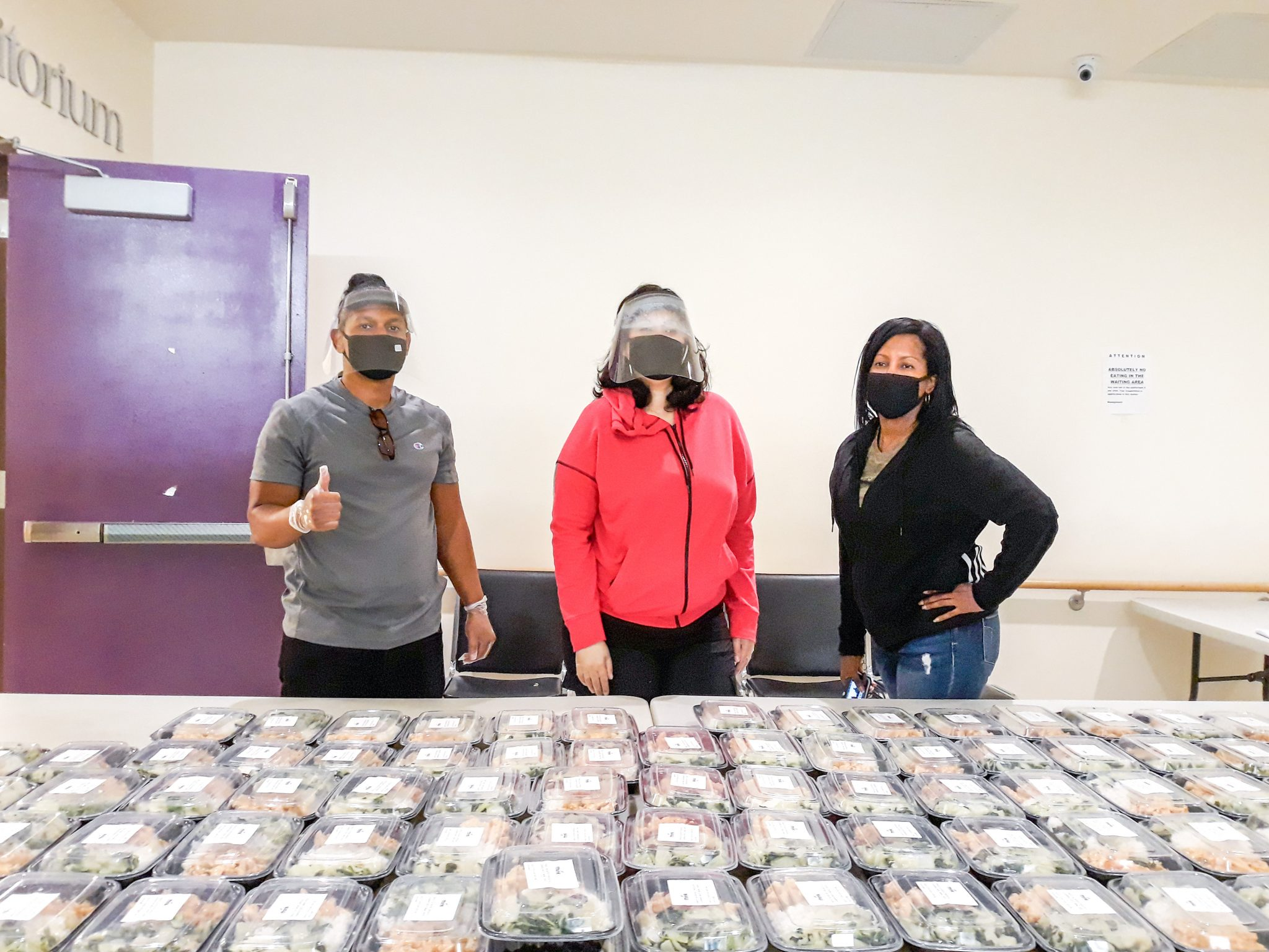 Three volunteers wearing masks stand in front of a large table filled with take-home plates of food.