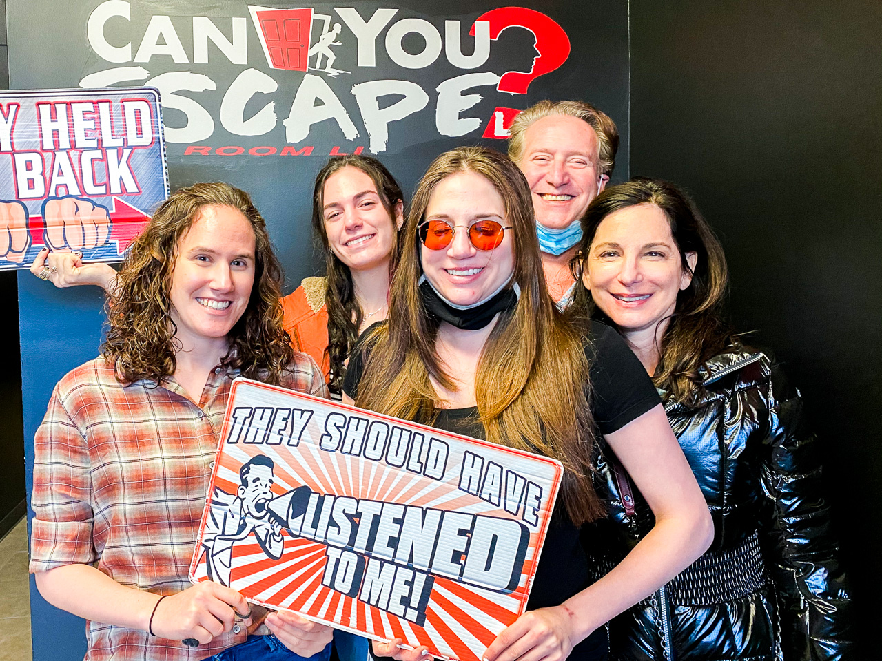 A family of 5 stand by each other inside of an Escape Room and hold up a sign