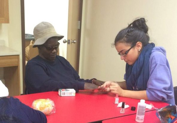 Young girl meticulously painting older lady's nails