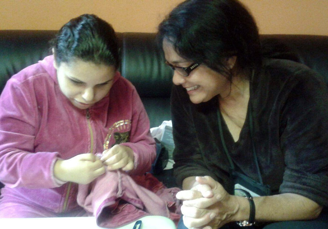 Lady in black helping girl in pink to sew