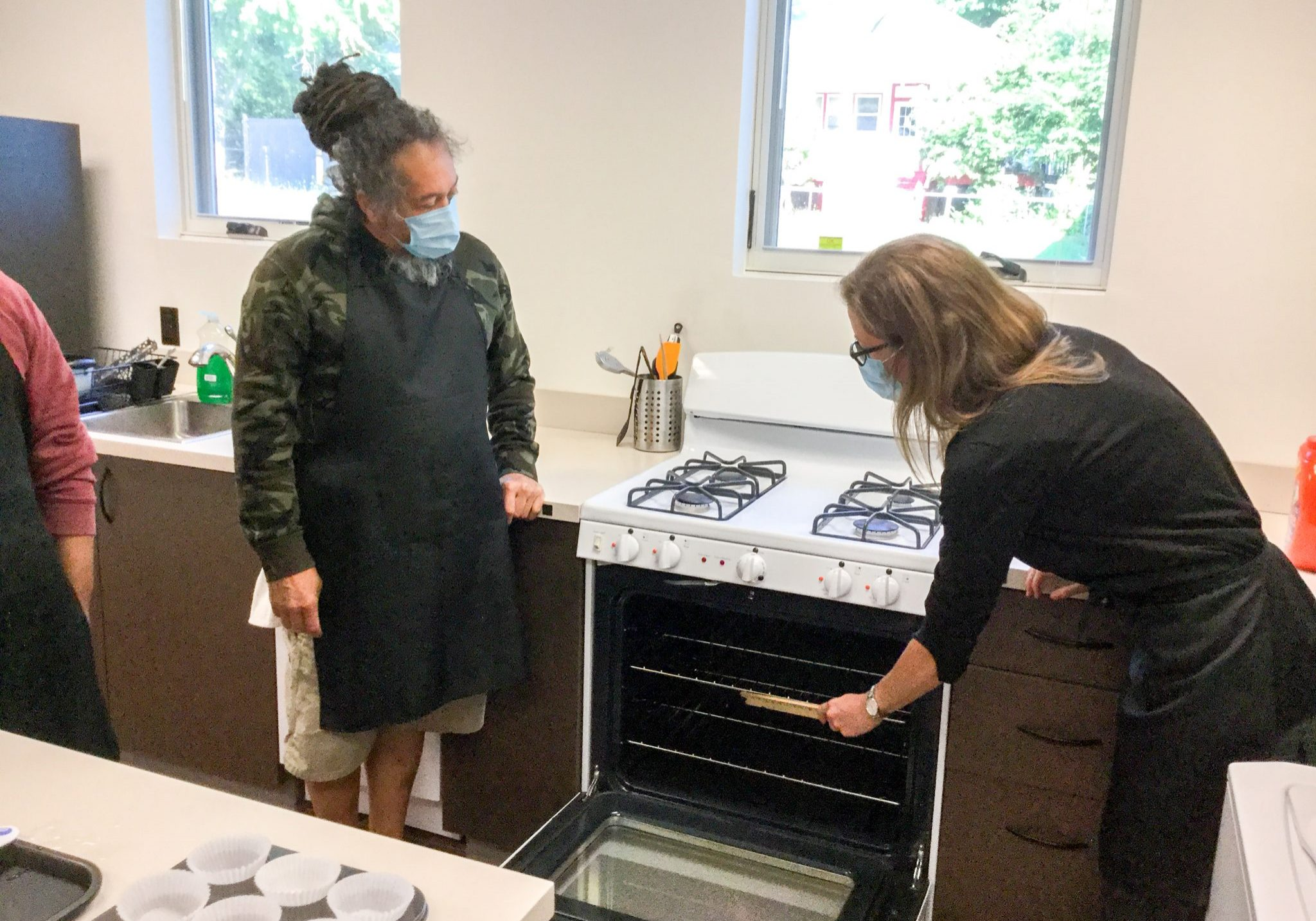 An instructor at VISIONS Vocational Rehabilitation Center works with two participants on safely using the oven.