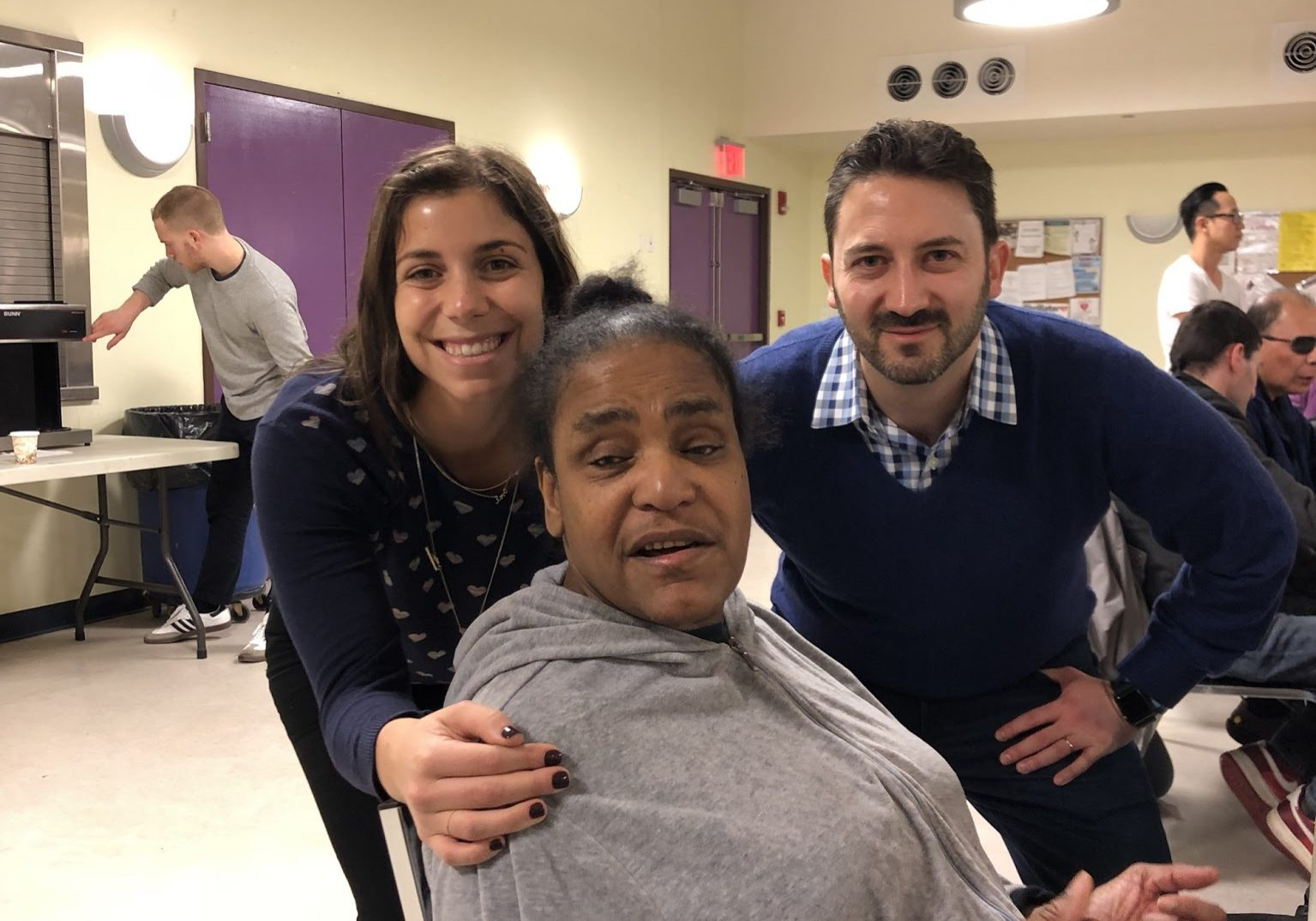 Participant Mary Conners with Volunteers from Bizzabo: three smiling faces from bingo night, while young man in background fumbles with coffee maker